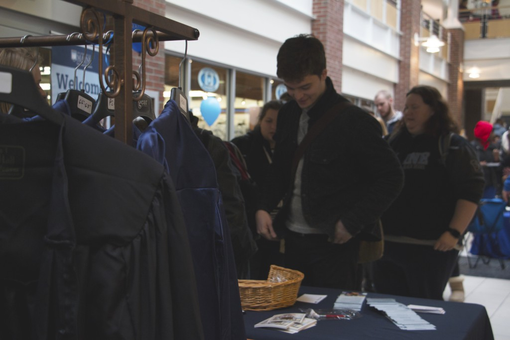 New Media senior William Mcenry orders his cap and gown at the 2016 University of Maine Grad Fair in order to walk in the graduation ceremony in May. Photo by Zach Davis, contributor.
