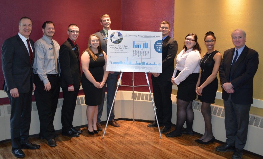 Students Representatives to the University of Maine System board of trustees present Chair Samuel Collins (far left) and Chancellor James Page (far right) with chart depicting Maine's status as the only state in the country to lower the real cost of four-year, public higher education.  Photo courtesy of UMS.