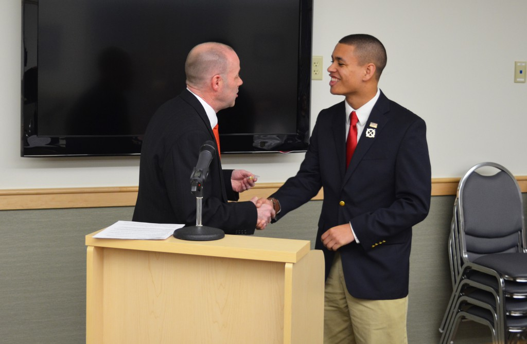University of Maine student Lee Jackson shakes Old Town city council president David Mahan's hand as he is given the key to the city of Old Town during a city council meeting at city hall on April 4. Photo by Ian Ligget, staff.